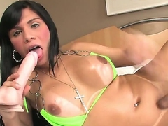 The hot shemale Fabiola Ribeiro is in the raunchy masturbation session erotically sucking the big dildo toy and at the same time hardly wanking her own sticking hard piston