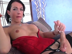 Dark haired and sexy shemale Danika Dreamz in her provocative corset and lingerie wanks her big and sitff dick on the couch and cums all over herself in front of the camera.