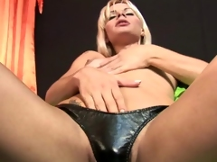 Salacious blonde tranny Thays Schiavinato touching her small breasts and playing with her hard cock